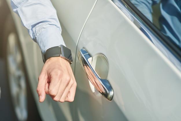 Gros plan d'une main masculine avec un homme smartwatch va ouvrir la voiture tout en se tenant à l'extérieur