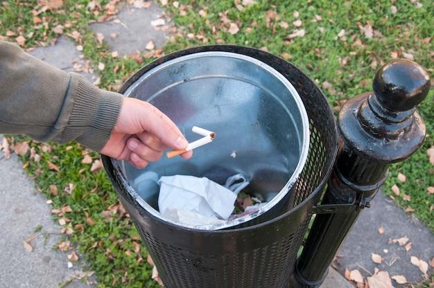 Gros plan d'une main masculine jetant une cigarette cassée à la poubelle.
