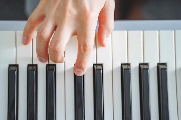 Gros plan sur une main masculine jouant du piano électrique. arrière-plan. vue de dessus.