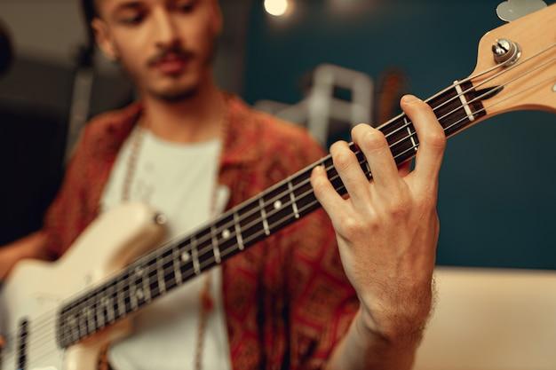 Gros plan de la main masculine jouant de la guitare électrique dans l'obscurité