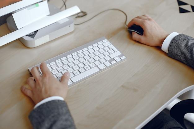 Gros plan d'une main masculine occupée à taper sur un ordinateur portable. homme au bureau.