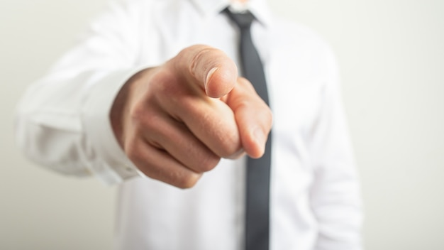 Gros plan de la main masculine pointant l'index vers vous.