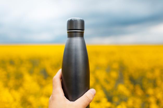 Gros plan d'une main masculine tenant une bouteille d'eau thermo en acier noir sur fond de champ de colza flou.
