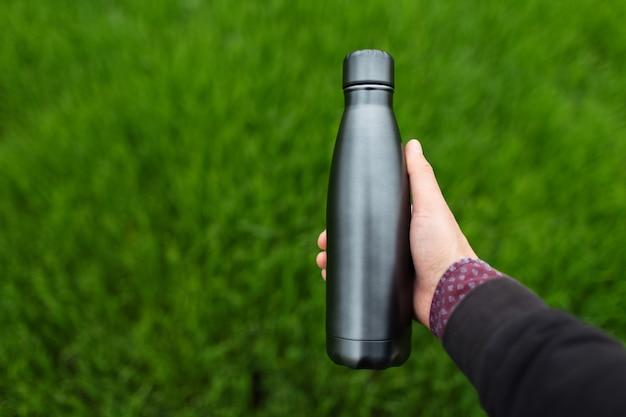 Gros plan d'une main masculine tenant une bouteille d'eau thermo réutilisable en acier sur fond d'herbe verte floue avec espace de copie.