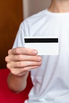 Gros plan sur une main masculine tenant une carte de crédit blanche.