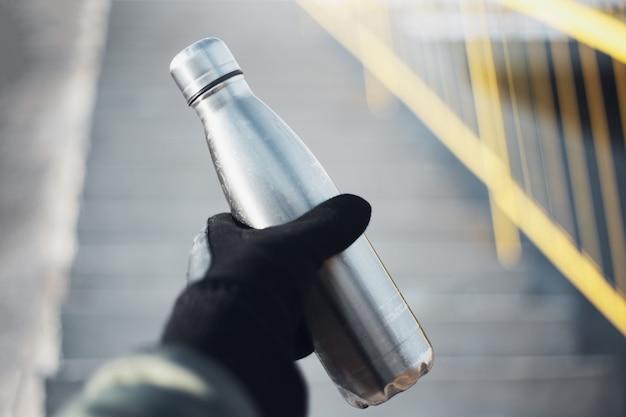 Gros plan d'une main masculine tenant un gant noir habillé, tenant une bouteille d'eau thermo en acier réutilisable sur le mur flou des escaliers urbains.