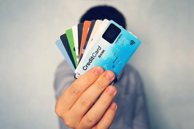 Gros plan sur une main masculine tenant une pile de cartes de crédit multicolores sur fond bleu clair flou. homme montrant des cartes de paiement avec de nouvelle génération. technologie de numérisation d'empreintes digitales dans le secteur bancaire. de nombreux.