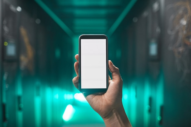 Gros plan sur une main masculine tenant un smartphone avec un écran blanc vierge dans une salle de serveur futuriste, espace pour copie