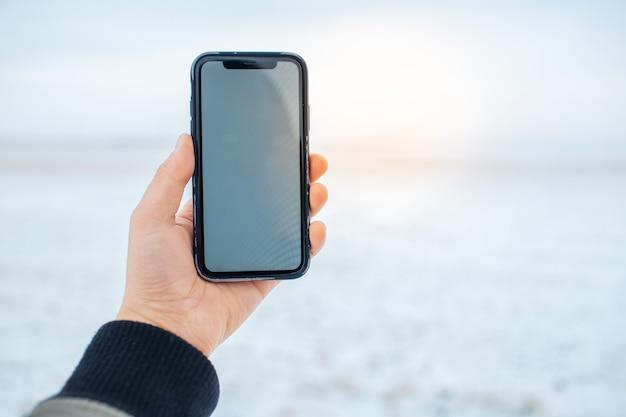 Gros plan d'une main masculine tenant un smartphone avec une maquette sur fond de champ neigeux flou. effet de lumière du soleil.