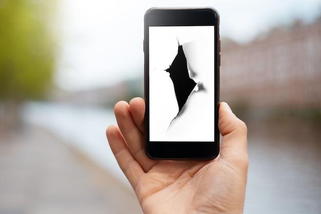 Gros plan sur une main masculine tenant un smartphone avec un trou dans du papier blanc à l'écran sur un arrière-plan flou de la ville.