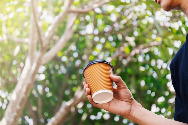 Gros plan d'une main masculine tenant une tasse de café en papier à emporter.