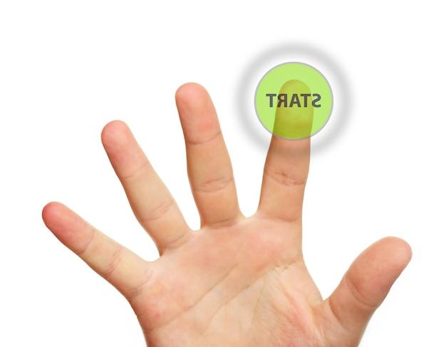 Un gros plan d'une main masculine touchant le bouton de démarrage