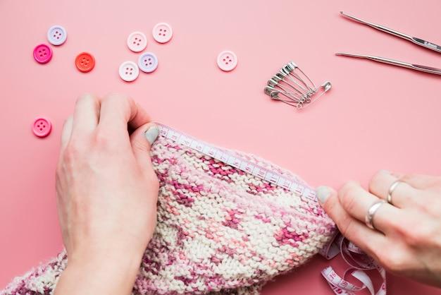 Gros plan d'une main mesurant le tricot avec du ruban adhésif sur fond rose