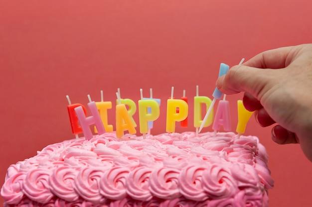 Gros plan de la main mettant la bougie de gâteau sur le gâteau d'anniversaire avec copie espace isolé sur mur rouge