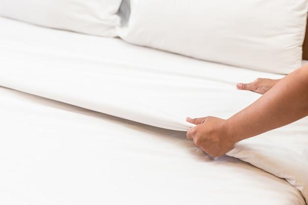 Gros plan main mis en place un drap blanc dans la chambre d'hôtel
