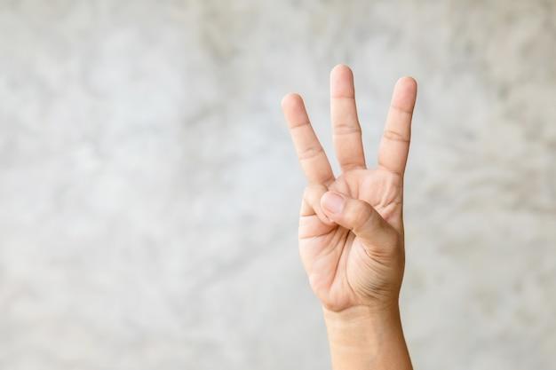 Gros plan main montrant le symbole de trois doigts