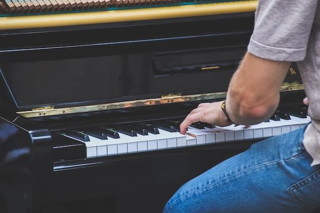 Gros plan main musicien jouant du piano à l'extérieur.