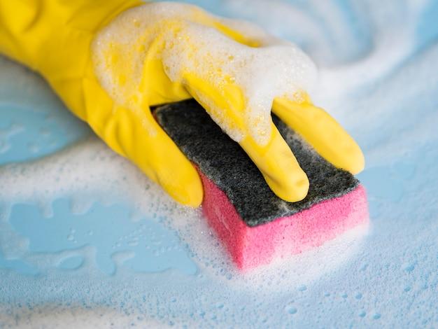 Gros plan main avec nettoyage des gants en caoutchouc