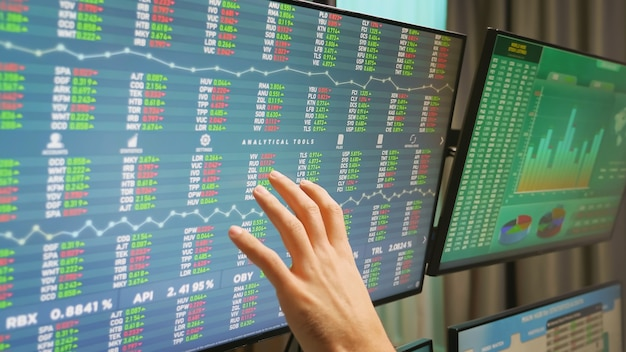 Gros plan sur la main d'un opérateur boursier sur des moniteurs avec des graphiques financiers.