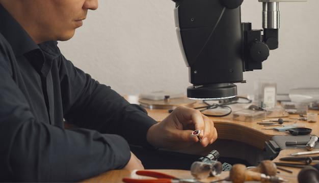 Gros plan sur une main d'orfèvre décorant une bague précieuse avec de belles pierres précieuses. bijoutier professionnel regardant la bague dorée finie. concept de production de bijoux en or.