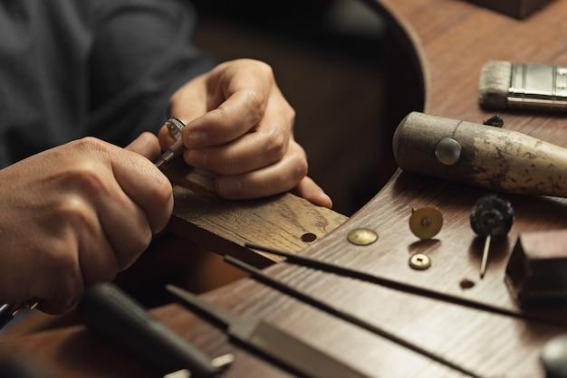 Gros plan d'une main d'orfèvre polissant une précieuse bague en or avec des diamants brillants pour faire le je...