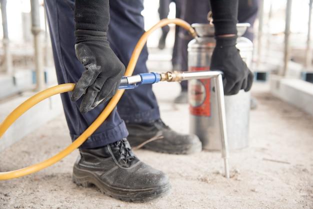 Gros plan de la main d'ouvrier de lutte antiparasitaire tenant le pulvérisateur pour la pulvérisation de pesticides sur le cabinet