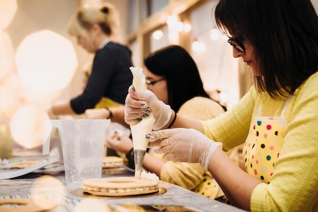 Gros plan d'une main de pâtisserie décorant un pain d'épice de noël avec une poche à douille, ambiance de travail. vue sur l'épaule.