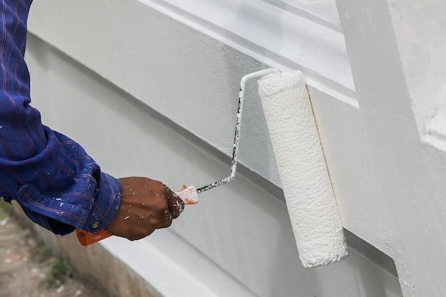 Gros plan de main de peintre en gant blanc, peignant un mur avec rouleau à peinture