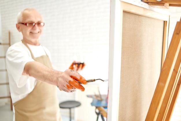Gros plan de la main d'un peintre masculin âgé, peignant ses derniers coups de pinceau, ses doigts brodés à la peinture orange.