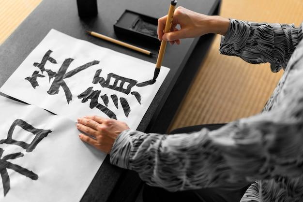 Gros plan main peinture lettres japonaises