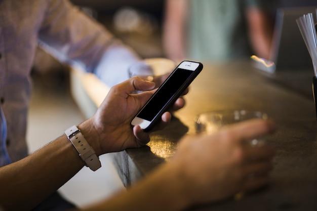 Gros plan de la main de la personne à l'aide de téléphone portable au bar comptoir