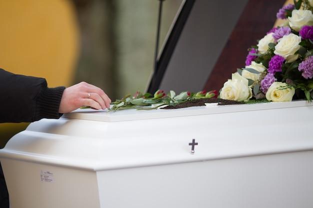 Gros plan d'une main de personne sur un cercueil avec un arrière-plan flou