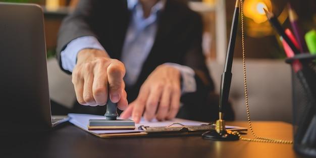Gros plan sur la main d'une personne estampée avec un tampon approuvé sur le document de certificat d'approbation papier public au bureau, notaire ou hommes d'affaires travaillent à domicile, isolés pour la protection contre le coronavirus covid-19
