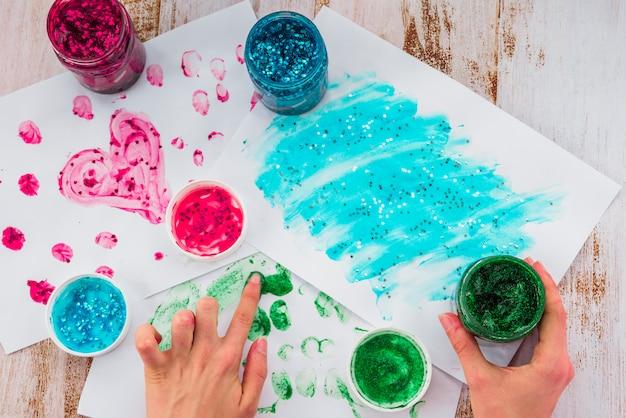Gros plan de la main d'une personne faisant de la peinture au doigt avec des couleurs de paillettes