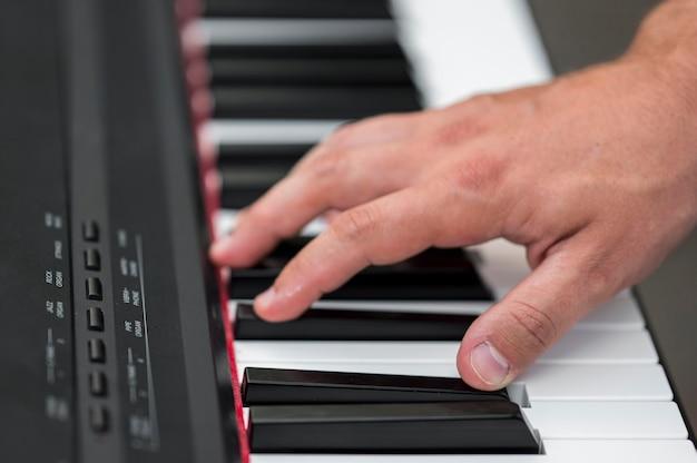 Gros plan main sur piano numérique