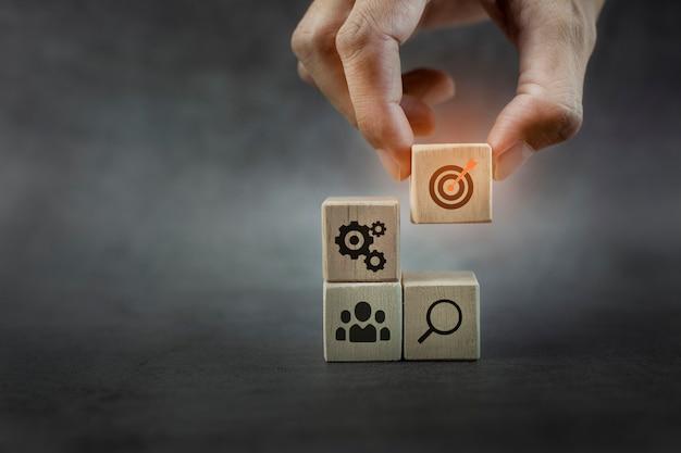 Gros plan main pile bois bloc étape sur table avec icône stratégie commerciale et plan d'action