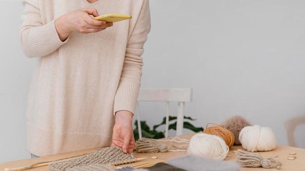 Gros plan main posant article tricoté avec téléphone