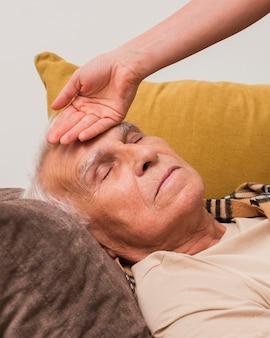 Gros plan main prenant la température du vieil homme