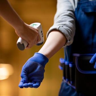 Gros plan main prenant la température à portée de main