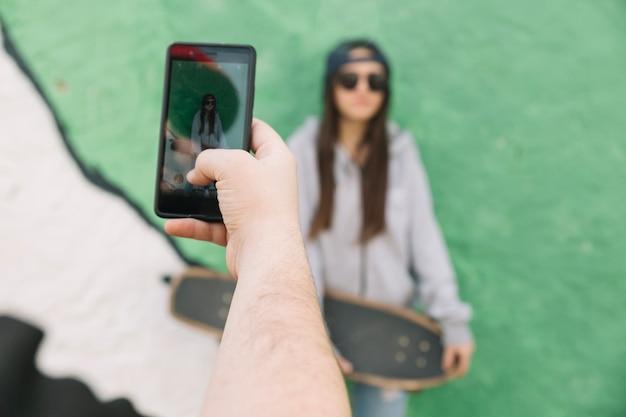 Gros plan, de, a, main, prendre, photographie, de, a, femme, tenue, skateboard
