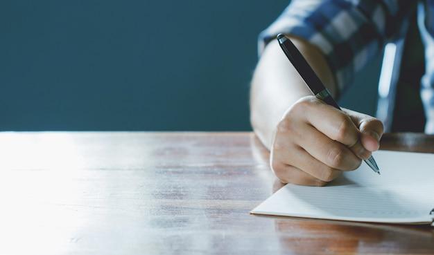 Gros plan d'une main qui tient un stylo, c'est comme un écrivain. idée créative de travail objectifs 2019, écriture, dessin, prendre des notes dans le document. affaires, investissement, concept, vintage, style d'humeur naturelle rétro.
