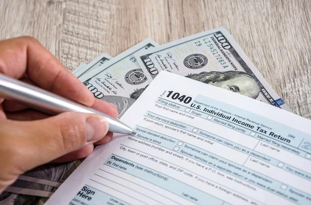 Gros plan d'une main remplit le formulaire d'impôt 1040