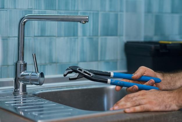 Gros plan de la main d'un réparateur professionnel tenant une clé à pipe tout en fixant le robinet dans le