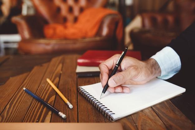 Gros plan de la main avec un stylo écrit dans le cahier.