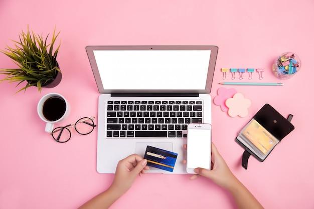 Gros plan de la main en tapant sur un ordinateur portable avec carte de crédit à utiliser acheter en ligne