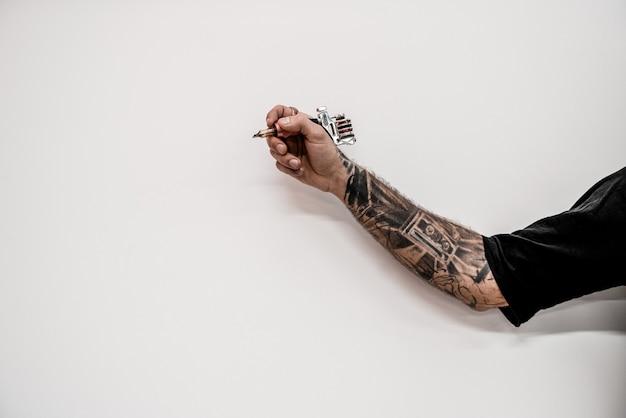 Gros plan de la main tatoueur hipster à l'ancienne tenant la machine à tatouer sur un fond blanc.