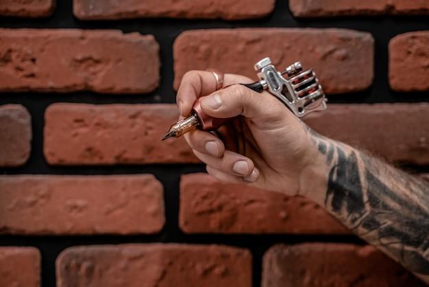 Gros plan de la main tatoueur hipster à l'ancienne tenant la machine à tatouer sur un fond de brique.