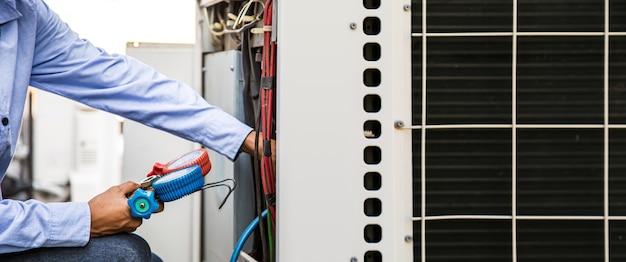 Gros plan sur la main d'un technicien utilisant une jauge de collecteur pour remplir les climatiseurs.