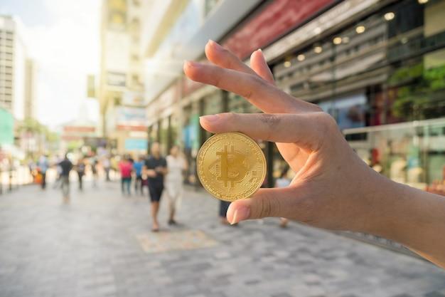 Gros plan main tenant bitcoin sur la photo floue du magasin de magasinage