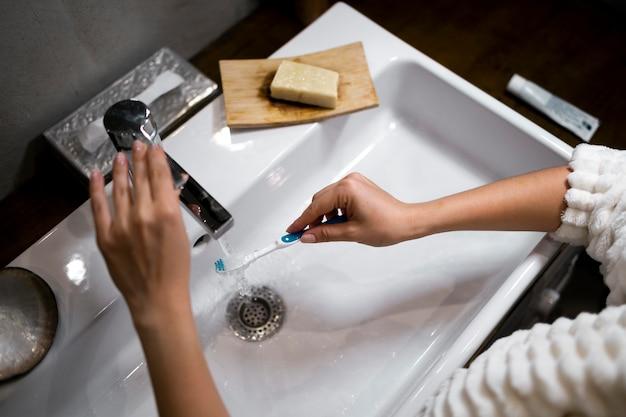 Gros plan main tenant une brosse à dents